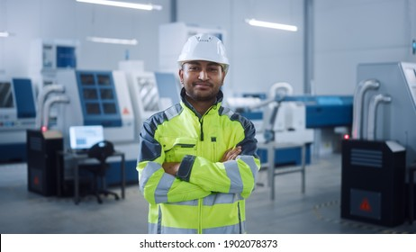 Portrait of Handsome Indian Engineer Wearing Safety Vest and Hardhat Smiles with Crossed Arms. Professional Man Working in the Modern Manufacturing Factory. Facility with CNC Machinery and robot arm