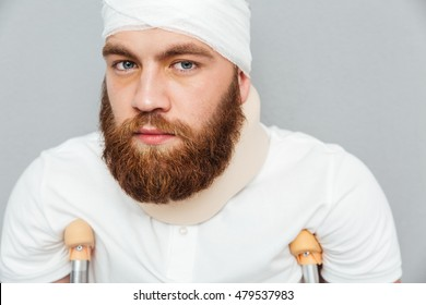 Portrait of handsome injured young man with crutches over white background