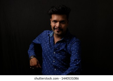 Portrait of a handsome and intelligent Indian brunette man wearing blue shirt with white stars sitting on a chair. Indian lifestyle and fashion portrait