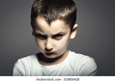 Portrait of handsome kid with angry face against grey background.