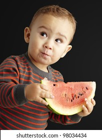 portrait of a handsome kid holding a watermelon and tasting over