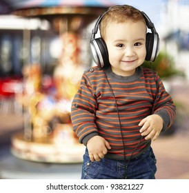 portrait of a handsome kid listening to music and smiling against a carousel background
