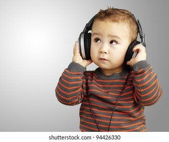 portrait of a handsome kid listening to music looking up over grey background