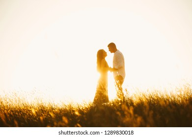 Portrait of handsome kissing couple on sunset or sunrise in meadow