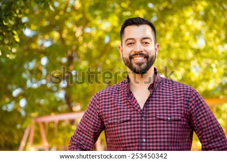 Portrait of a handsome Latin young man with a beard hanging out outdoors