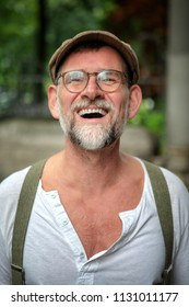 portrait of handsome laughing bearded man with hat and eyeglasses in his 50s