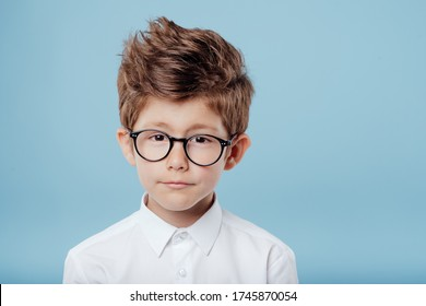 portrait of handsome little boy in glasses look at the camera, isolated on blue background