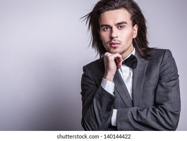 Portrait of handsome long-haired stylish man with bow tie.