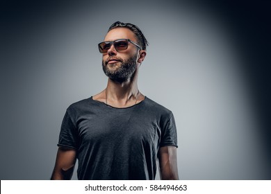Portrait of handsome macho male dressed in a grey t shirt and sunglasses isolated on grey background.
