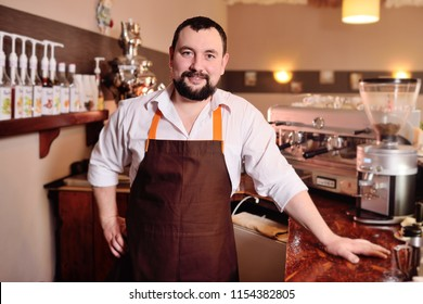 portrait of a handsome male barista in an apron on the background of a cozy coffee house and a coffee machine.