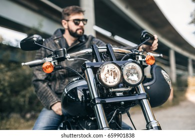 Portrait of a handsome male biker and wearing glasses. Close-up of motorcycle, headlights and steering wheel.