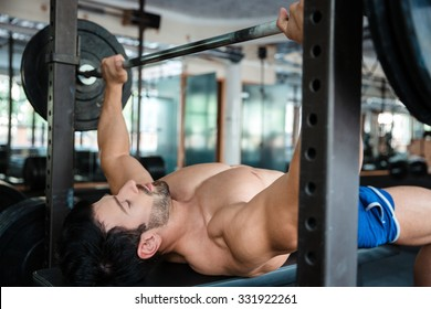 Portrait of a handsome male bodybuilder doing bench press in fitness gym