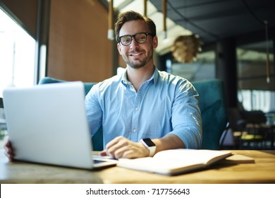 Portrait of handsome male CEO in trendy eyeglasses satisfied with occupation working on creative project using technology, prosperous businessman making plans for start-up sitting in coffee shop