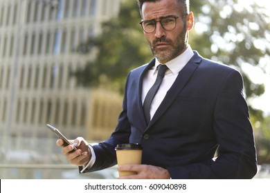 Portrait of Handsome male confident mature businessman dressed in fashionable suit using 4G internet connection on mobile phone.Businessman looking to camera with smartphone in hands standing outdoors