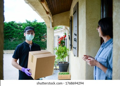 Porträt eines gut aussehenden männlichen Ablieferers, der das Paket zu Hause an eine weibliche Klientin ausliefert, mit Maske-Handschuhen und Schutzbrille gegen eine Covid19-Infektion mit dem Coronavirus-Virus