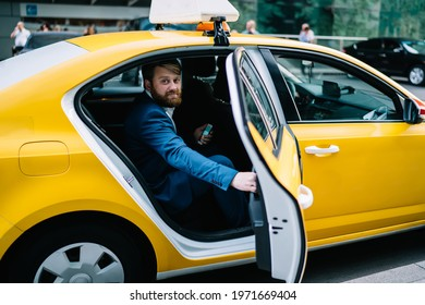 Portrait of handsome male economist sitting at yellow cab and closing automobile door while hurry up to business meeting with corporate boss of enterprise, Caucasian man lawyer in taxi transport