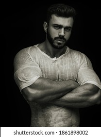 Portrait of handsome male fitness model crossing his arms