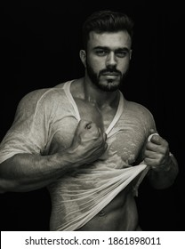 Portrait of handsome male fitness model holding his wet tshirt in sepia tone