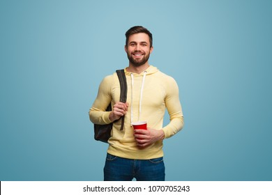 Portrait of handsome male model in casual outfit holding cup and backpack on shoulder smiling at camera.