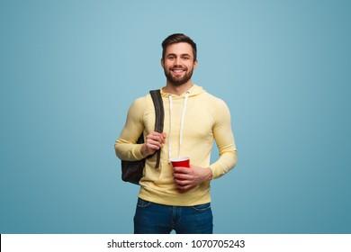 Portrait d'un beau mannequin mâle en tenue décontractée tenant une tasse et un sac à dos sur l'épaule souriant à la caméra.