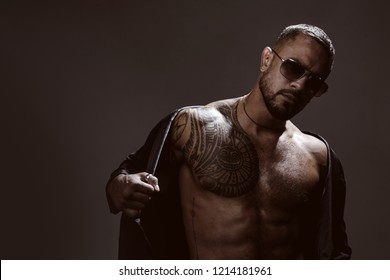 Portrait of handsome male model in fashion jacket and stylish glasses. Confident and handsome Brutal man looking away. Man glasses. Sexy model in aviator sunglasses.