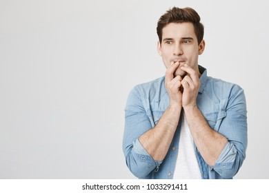 Portrait of handsome male with thoughtful expression, touching folded lips with fingers while planning something in mind, isolated over white background. Guy decides to buy new gadget