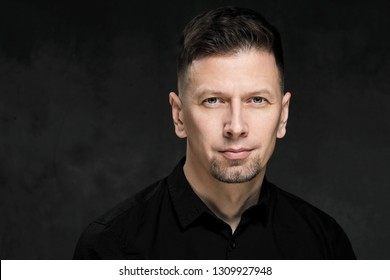Portrait of a handsome man 40 years old on a dark artistic background close-up. Brunette, with gray hair, black beard and black shirt. Confident and serious look.