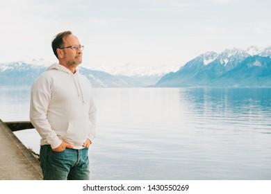 Portrait of handsome man admiring beautiful lake with mountains, wearing white sweatshirt