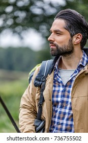 portrait of handsome man with backpack looking away