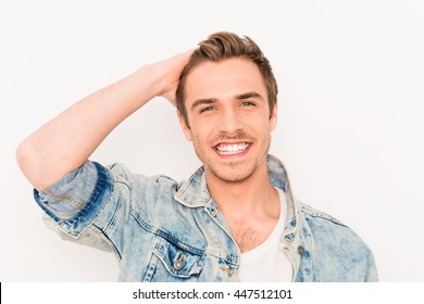 Portrait of handsome man with beaming smile touching his hair