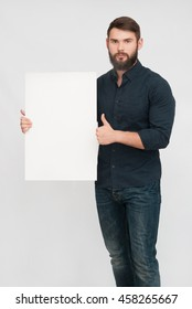 Portrait of handsome man with beard and board. Handsome man holding board or white blank