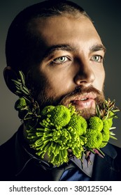 Portrait of a handsome man with a beard of green flowers. Men's beauty. Barbershop.