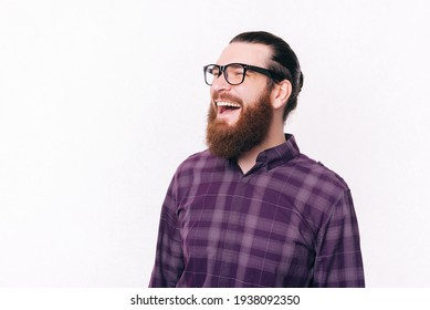Portrait of handsome man with beard wearing eyeglasses and laughing.