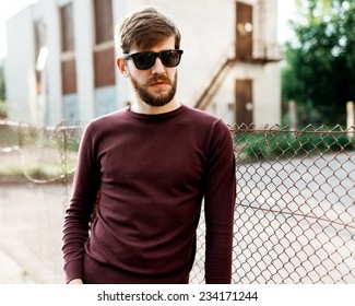 Portrait of a handsome man with a beard wearing glasses on a sunny day
