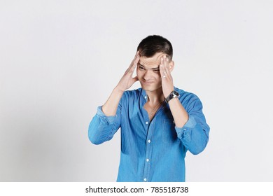 Portrait of handsome man in blue jeans shirt with glasses touching his temples feeling stress, on white background. Headache concept. STRESS CONCEPT.
