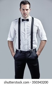 Portrait of handsome man with bow tie and suspenders isolated over grey