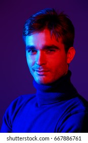 Portrait of a handsome man with bristle in blue and red light. Male beauty, fashion.