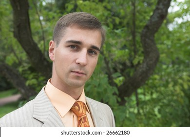 Portrait of a handsome man in business suit during his walk in a park