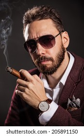 Portrait of handsome man in casual dress smoking a cigar.
