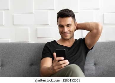 Portrait of Handsome man in casual is using smartphone and sitting on sofa. Happy young male relaxing over white wall .