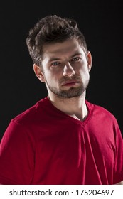 A portrait of a handsome man with dark brown hair in a red T-shirt