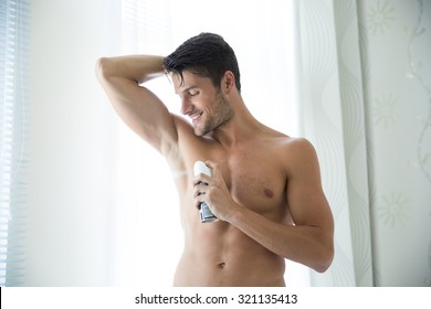 Portrait of a handsome man with deodorant at home