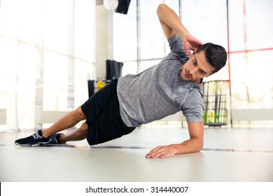 Portrait of a handsome man doing side plank at gym
