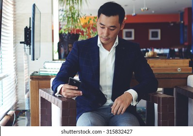 Portrait of handsome man dressed in luxury clothes chatting on his smart phone while sitting in cozy coffee shop inside, confident man entrepreneur using cell telephone while relaxing in cafe