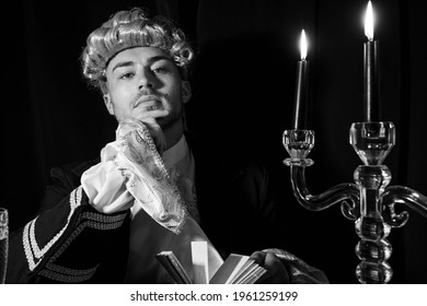 Portrait of handsome man dressed in regency costume and wig sitting at writing desk.