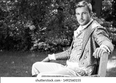 Portrait of handsome man dressed in vintage costume sitting on bench in garden