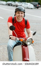 Portrait of a handsome man driving a bike in city. Broad smile of the guy holding handlebars.