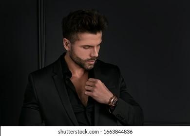 Portrait of handsome man in elegant black suit posing. Men's beauty, fashion.