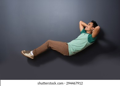portrait of a handsome man floating with sleeping pose isolated on dark background