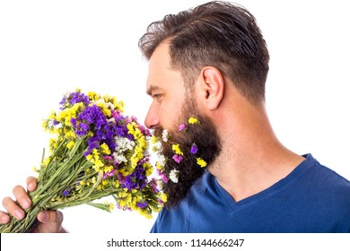 Portrait of a handsome man with flowers in beard smelling a bouquet of flowers on white